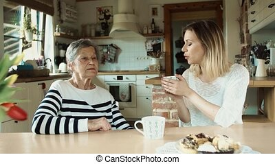 Elderly grandmother with an adult granddaughter eating biscuits at home.