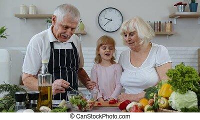 Elderly grandparents in kitchen feeding grandchild girl with...