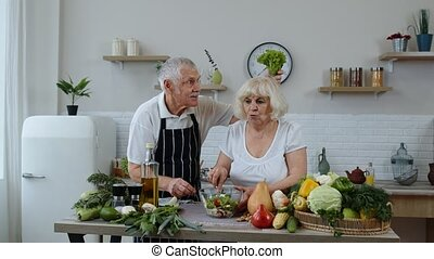 Elderly grandparents in kitchen. Funny grandpa joking on grandma. Putting a lettuce about her head