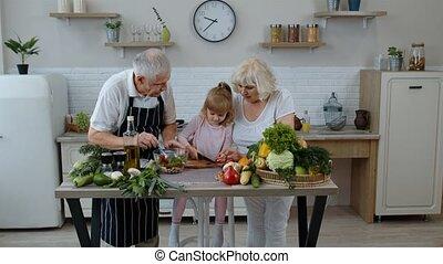 Elderly grandparents in kitchen teaching grandchild girl how...