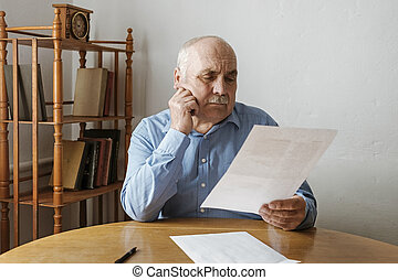 Elderly grey haired man with mustache reading