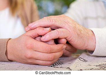 Elderly hands holding carer's hands