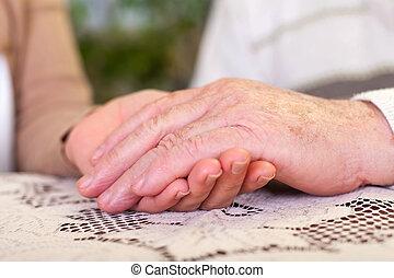 Elderly hands holding carer's hands