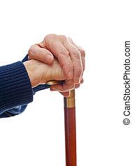 Elderly hands resting on stick