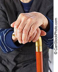 Elderly hands resting on stick - Elderly hands resting on...