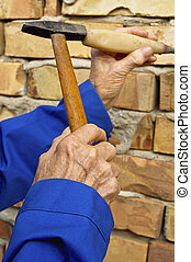 Elderly hands with a hammer and chisel.