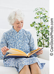 Elderly happy woman looking at her family album