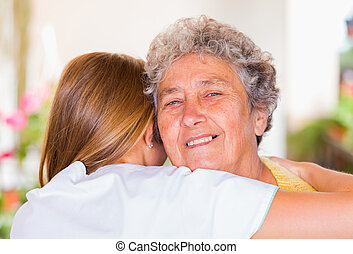 Elderly home care - Happy elderly woman embracing with her...