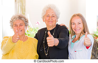 Elderly home care - Happy elderly women with their carer ...