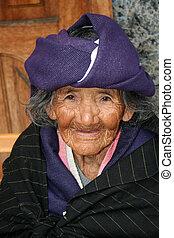 An elderly homeless woman smiles on the street in Cotacachi, Ecuador