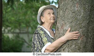 Elderly hugging tree trunk her hands in the forest