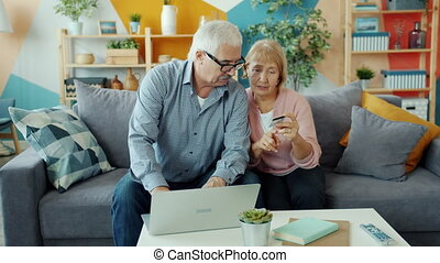 Elderly husband and wife are making money transaction with bank card and laptop at home enjoying modern technology and online shopping together.