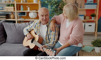 Elderly husband and wife singing while man playing the guitar enjoying music at home