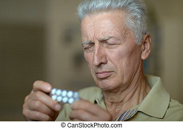 Elderly ill man  - Elderly ill man with pills in hand