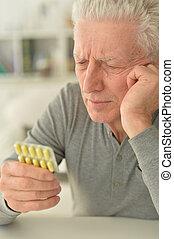 Elderly ill man with pills in hand