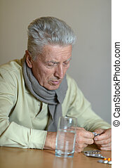 Elderly ill man with pills