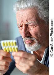 Elderly ill man with pills in hands