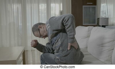 Elderly ill man with rheumatism stretching and massaging his...