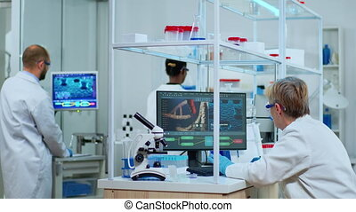 Elderly lab technician making pharmaceutical research for antibiotics, curing disease with DNA enhancing drugs. Multiethnic team examining virus evolution using high tech for treatment against covid19