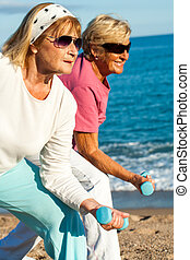 Elderly ladies doing worlout on beach.