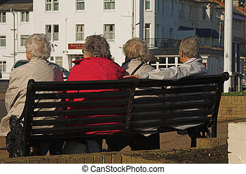 Four elderly ladies chatting on a bench