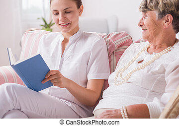Elderly lady and nurse reading