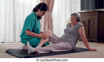 Elderly lady being rehabilitated by a physiotherapist at home