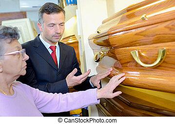 Elderly lady choosing coffin