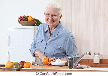 Elderly lady cutting an orange