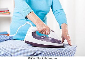 Elderly lady during ironing