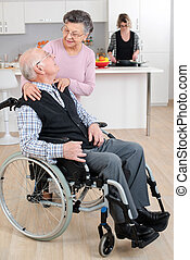 Elderly lady embracing husband in wheelchair
