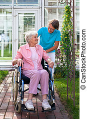 Elderly lady in a wheelchair with her carer