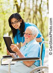 Elderly Lady in Wheelchair Reading