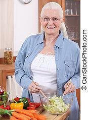 Elderly lady making a salad