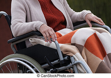 Elderly lady on wheelchair outdoors