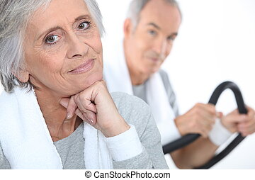 elderly lady posing in fitness center with husband in...