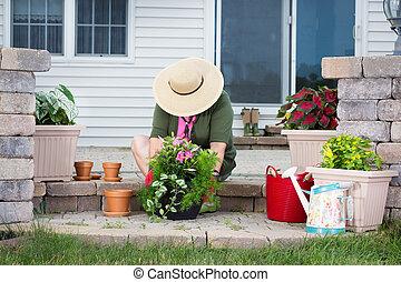 Elderly lady potting up new houseplants