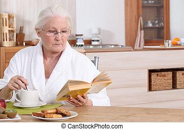 Elderly lady reading over breakfast