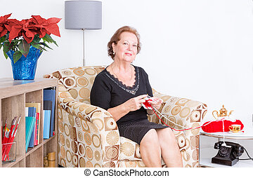 Elderly lady sitting in an armchair knitting
