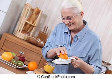 Elderly lady squeezing orange juice