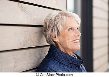 Elderly lady standing reminiscing