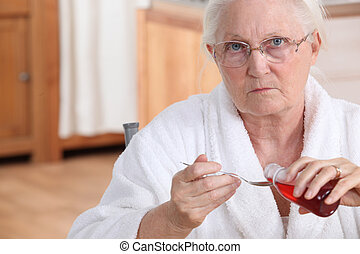 Elderly lady taking medication in kitchen