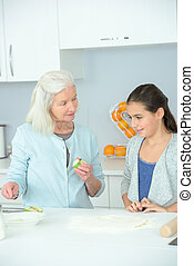 elderly lady teaching little girl how to cook