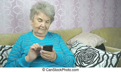 Elderly lady using a mobile phone sits on a sofa