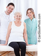 Elderly lady with her physiotherapists