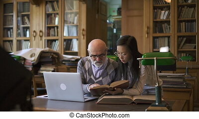 Elderly lecturer and young woman discussing theme at table in library.