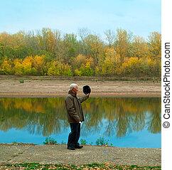 elderly man against coast of river