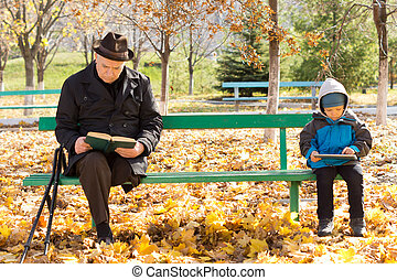 Elderly man and small boy sitting on a park bench