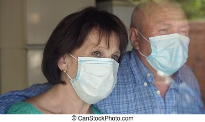 Elderly man and woman in face masks behind window