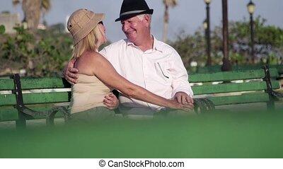 Elderly man and woman talking, kiss